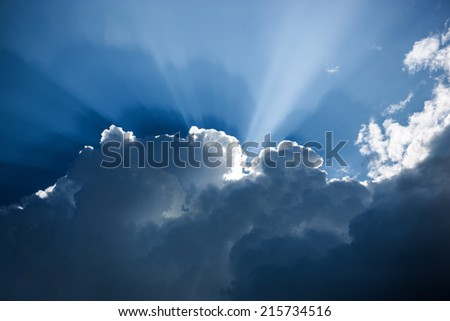 Impressive dark blue cloudscape with white cloud edges and sunbeams  - stock photo