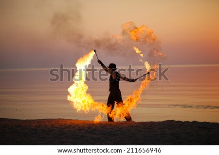 Impressive fire show; torch twirling on the beach - stock photo