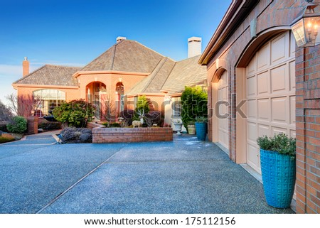 Impressive luxury house with colomn porch, tile roof, stoned walkway. Winter, snowy - stock photo