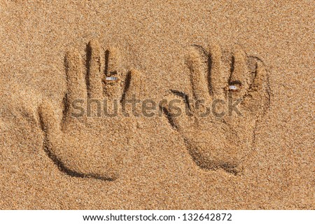 Imprint of two hands in the sand. Hands and wedding rings. - stock photo