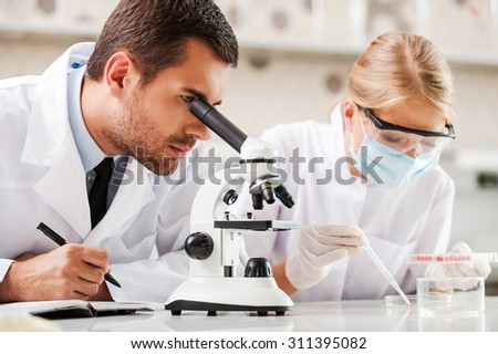 Improving modern medicine. Two young scientists making experiments while sitting in the laboratory - stock photo