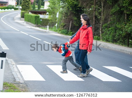 Imptatient Boy with his Family crossing the Road - stock photo
