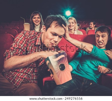 Impudent young man steals popcorn in cinema while people watching movie - stock photo
