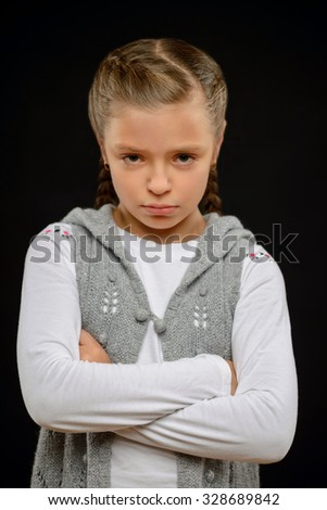 In a bad tamper. Little cheerless pretty girl folding her hands and feeling upset while standing isolated on black background - stock photo
