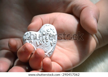 in a children's hand lies decoration - white heart. behind the man's hand