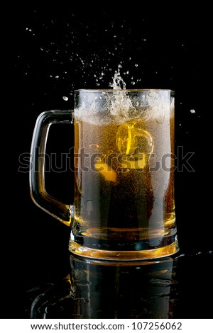 In a cold beer, threw a piece of ice on a black background.
