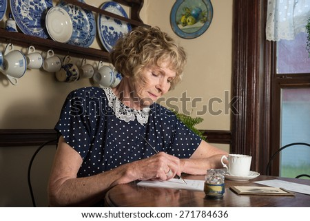 In a historical scene from the 1930??s or 1940s, an attractive elderly woman writes a letter as she sits at a table by a window. - stock photo