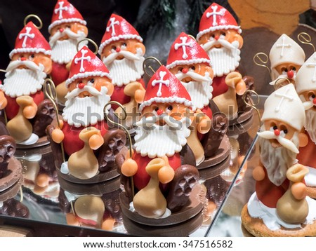 In a patisserie window, several examples of chocolate sweets with features of Santa Claus - stock photo