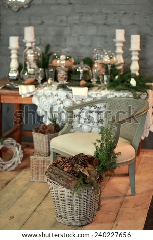in a room with a beautiful Christmas table decorations, chair and basket with pine cones - stock photo
