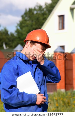 In a sad state working man in the helmet - stock photo