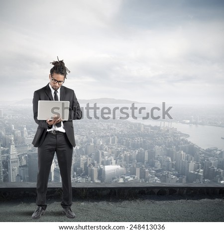 In a skyscraper businessman work with laptop - stock photo