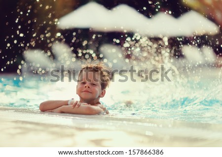 in a spray of water cute little boy bathes in pool - stock photo