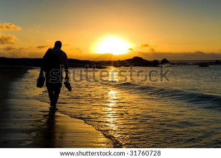 In a sunset scene a man walk on the beach just beside Cape Town, South Africa. - stock photo