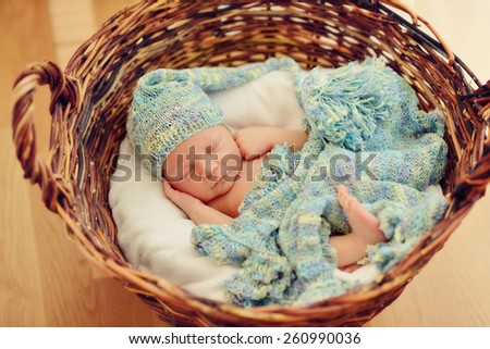 in a wicker basket brown cute sleeping baby in a blue cap with a large bubo - stock photo
