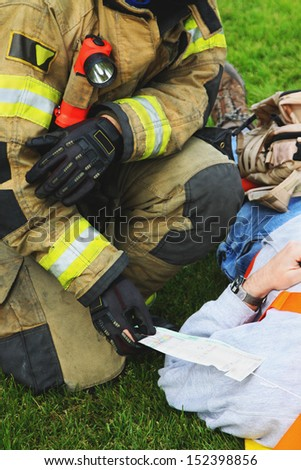 In any disaster or accidents victims receive medical attention. Medical tags are attached to them to track status. This fireman is checking on the injured status and card. - stock photo