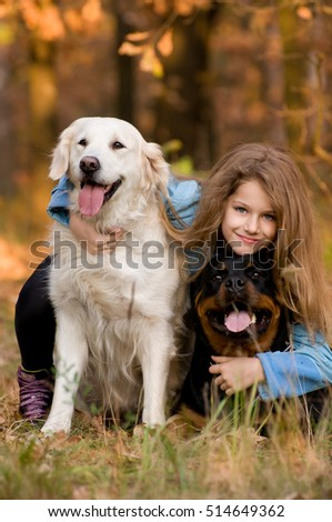 In autumn forest meadow preaty little girl lying on the grass with her golden retriever and black rottweiler  in the autumn forest. submissiveness. Best friends