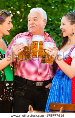 In Beer garden - friends in Tracht, Dirndl and Lederhosen drinking a fresh beer in Bavaria, Germany - stock photo