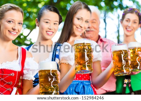 In Beer garden - friends, man and women in Tracht, Dirndl and Lederhosen drinking a fresh beer in Bavaria, Germany - stock photo