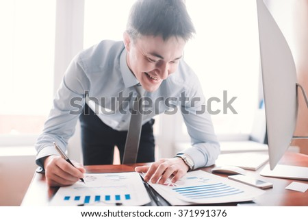 in blue shirt businessman checks the documents, looking at documents in his office smiling