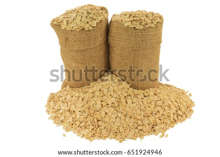 In Burlap Bags, spilled out on pile LARGE FLAKE OATS, ROLLED OATS FLATTENED BETWEEN ROLLERS to produce oatmeal on Large Flakes thick enough to hold shape during cooking isolated on white background