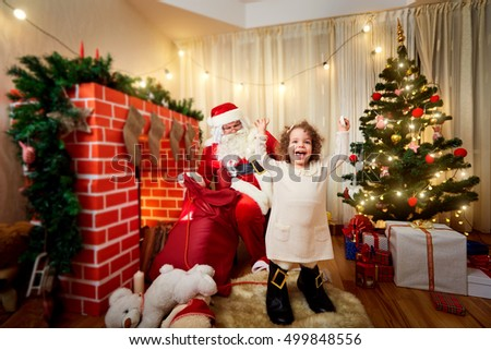 In Christmas curly little girl in boots with Santa Claus in the room laughing and having fun in the New Year gifts.