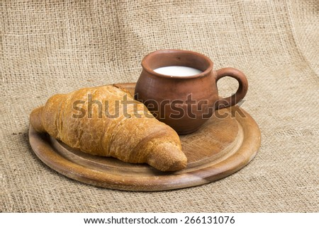 in clay cup poured milk, 2 croissants on a wooden stand, lie next to wheaten spikelets, sacking