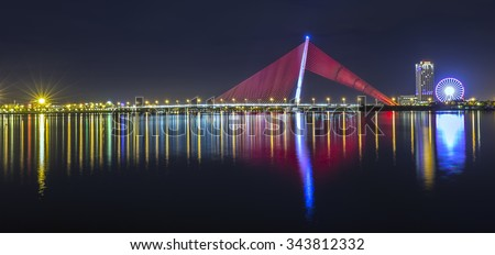 In Da Nang, Vietnam, 25th June, 2015: architectural beauty of light a sail shaped Tran Thi Ly Bridge shimmering mirror into the river at night create the beauty of the city of Da Nang, Vietnam