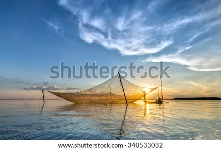 In Dong Nai, Vietnam - November 15th, 2015: fishermen mending their nets on his lift net as patch lifetime to grow more in the autumn afternoon in Tri An, Dong Nai, Vietnam