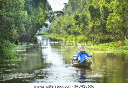 In Dong Thap, Vietnam - January 14th, 2014: Woman rowing on river passed house homeland with small body, shirt Ba Ba and conical hats typical of Southeast women in spring afternoon Dong Thap, Vietnam