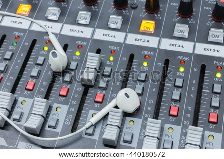 In ear monitors on a analog audio mixing console . - stock photo