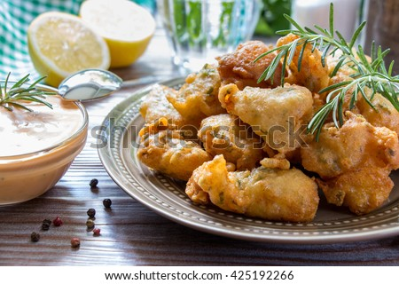 In foreground shrimps in crispy dough on a plate with rosemary and bowl of sauce near, in background glass of water, lemon, herbs, salt, pepper. Shrimps in pastry and sauce. Horizontal. Close. - stock photo