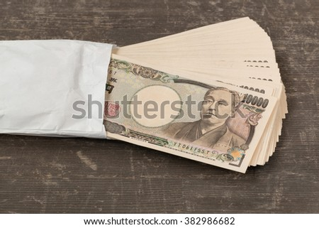 in front side of ten thousand yen japanese money in white  envelope on table - stock photo