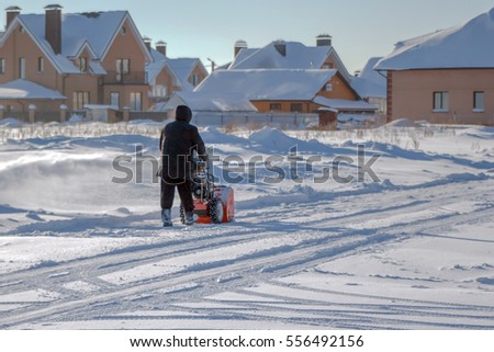 in frosty sunny day man cleans snow from the roadway harvesting technology