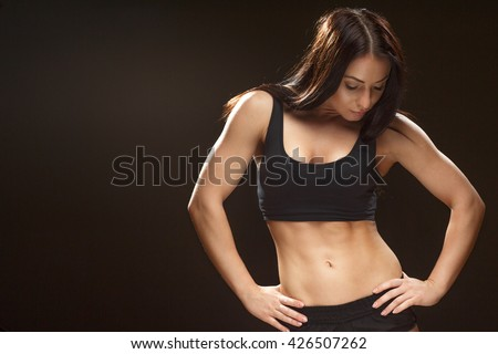 In great progress. Studio shot of an attractive female athlete posing at the studio looking down on her abs copyspace on the side on black background. - stock photo