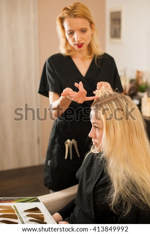 In hairdresser salon - hair stylist consulting a customer before doing her hairstyle - stock photo