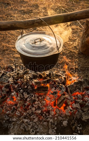 In hanging on a log cast iron cauldron on hot embers fading campfire stew boiling potatoes. Heated smoke rises in warm rays of evening sunset. Close-up view with space for text on blurred background - stock photo