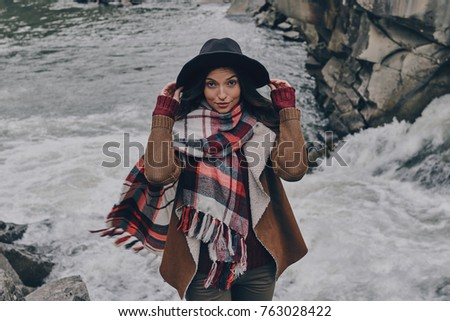 In her own style. Attractive young woman covered with blanket looking at camera while standing near the river in mountains