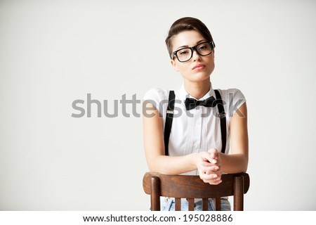 In her own style. Beautiful young short hair woman in white shirt and suspenders sitting on the chair and looking at camera - stock photo