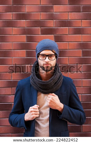 In his own style. Handsome young man in eyeglasses adjusting his jacket and looking at camera while standing against brick wall - stock photo