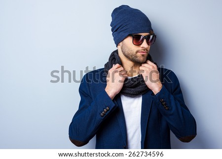 In his own style. Handsome young stylish man in sunglasses and hat adjusting his scarf and looking away while standing against grey background - stock photo