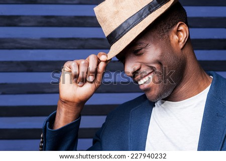 In his own unique style. Handsome young African man adjusting his hat and smiling while standing against striped background - stock photo