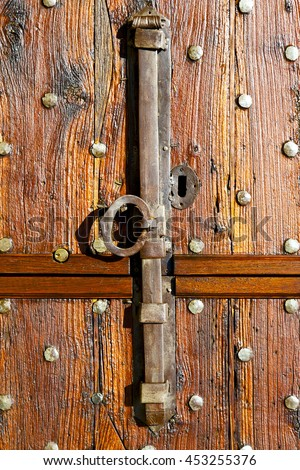 in  italy  patch lombardy    cross milan blur   abstract   rusty brass brown knocker  a  door curch  closed wood