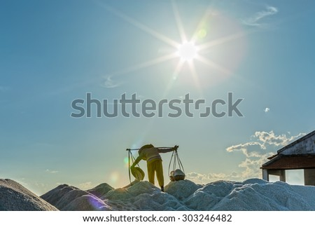 In Khanh Hoa, Vietnam, June 30, 2015: A farmer was carrying and pouring salt into piles on a sunny afternoon in the Hon Khoi salt field, Khanh Hoa, Vietnam - stock photo