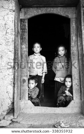 In Lao Cai, Vietnam - September 27th, 2015: the eyes of the children of farming parents waiting in doorway of the house made of soil in autumn afternoon in rural mountainous area of Lao Cai, Vietnam - stock photo