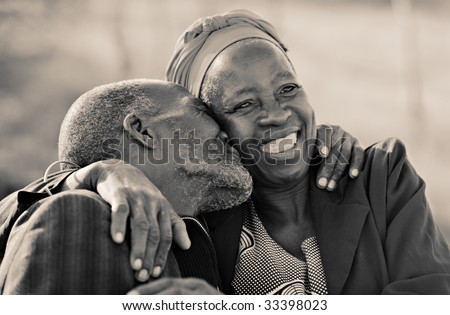 in love African American couple in their eighties and seventies, hugging and kissing, Botswana - stock photo