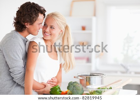 In love couple hugging while cooking in their kitchen - stock photo