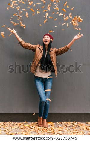 In love with autumn. Full length of beautiful young woman throwing orange fallen leaves and smiling while standing against grey wall outdoors  - stock photo