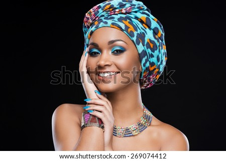 In love with her style. Beautiful African woman wearing a headscarf and jewelry and smiling while standing against black background - stock photo