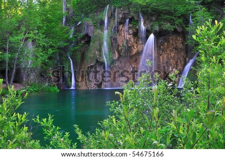 In midst of a forest waterfalls flow into a natural pool of green water - stock photo