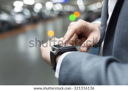 In parking car a man using his smartwatch. Close-up hands - stock photo